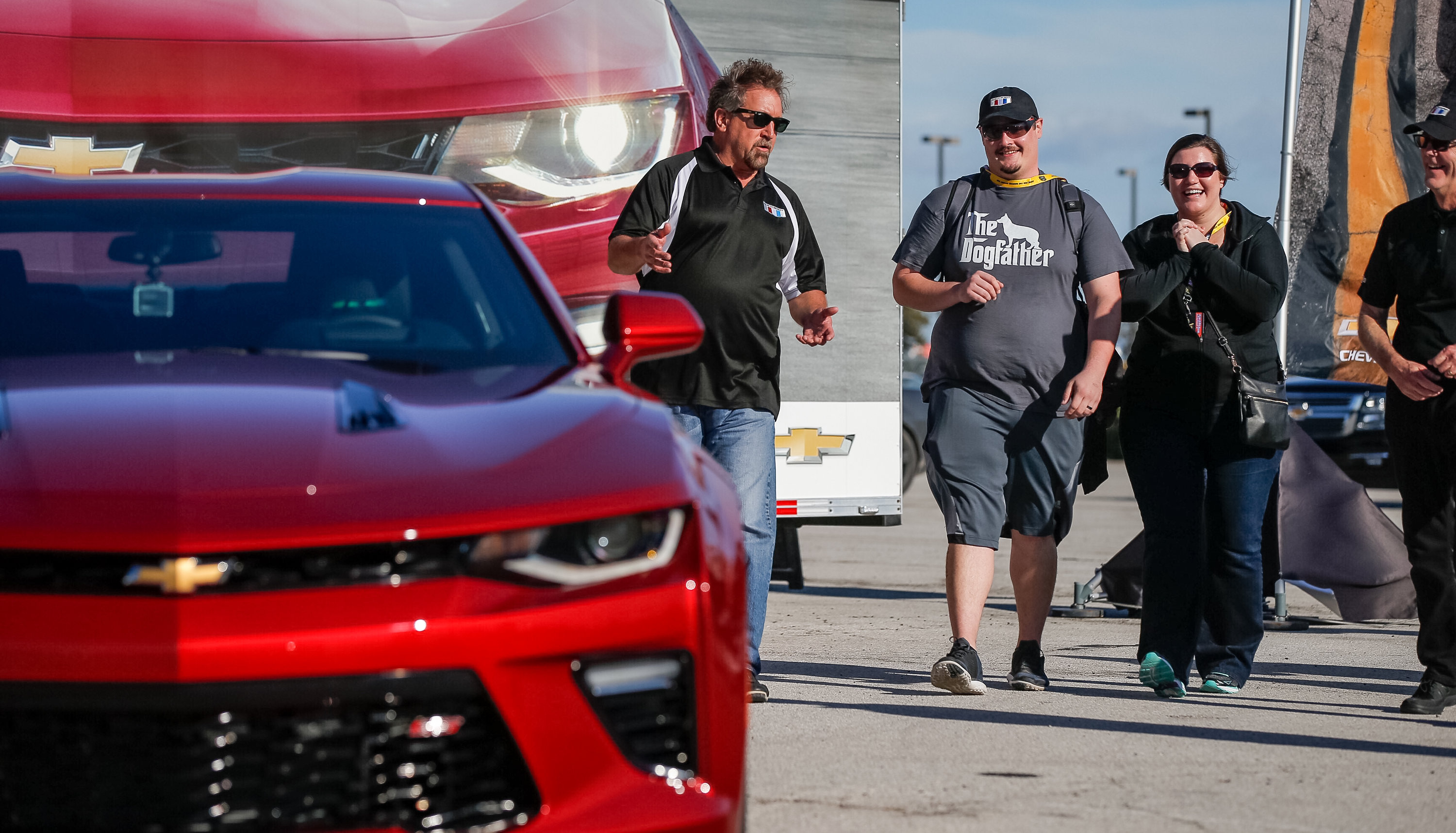 "Chevrolet Camaro Chief Engineer Al Oppenheiser (left) and Camaro Design Director Tom Peters (right) walk Alican ""Turk"" Boyacioglu of Wichita, Kansas and his wife Michelle to the first sixth-generation Chevrolet Camaro Saturday, November 7, 2015 in Dallas, Texas. Team Chevy race driver Danica Patrick surprises Boyacioglu by handing him the keys to the vehicle that he ordered through the Huffiness Chevrolet dealership in Dallas. The first wave of Camaro production models has begun shipping and should arrive at dealerships for customer delivery by mid-November. (Photo by Brandon Wade for Chevrolet)"